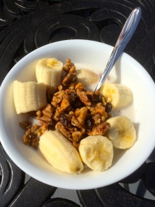 My Paleo granola as a bowl of cereal with almond milk and sliced banana.
